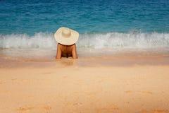 La giovane bella donna in costume da bagno ed il cappello che si rilassa su Navagio tirano, isola di Zacinto, Grecia fotografia stock libera da diritti