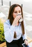 La giovane bella donna di affari beve il caffè ed il cellulare di uso fotografia stock libera da diritti