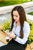 La giovane bella donna di affari beve il caffè ed il cellulare di uso immagini stock libere da diritti