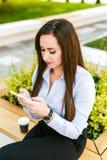 La giovane bella donna di affari beve il caffè ed il cellulare di uso fotografia stock