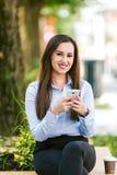 La giovane bella donna di affari beve il caffè ed il cellulare di uso immagine stock