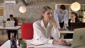 La giovane bella donna di affari sta guardando le notizie sul computer portatile in ufficio, tossente, la gente sta discutendo le video d archivio