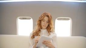 La giovane bella donna di affari sta scrivendo la seduta sullo strato nell'interno dell'aeroplano video d archivio