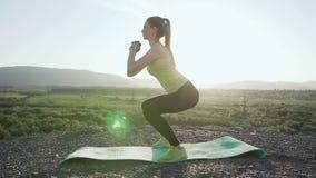 La giovane bella donna di sport che fa gli sport in montagna superiore sopra il fiume sull'alba, mattina si esercita, sano stock footage