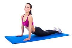 La giovane bella donna esile che fa l'allungamento si esercita su yoga mA Immagine Stock Libera da Diritti