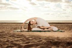 La giovane bella donna esile pratica l'yoga sulla spiaggia ai sunris Immagini Stock Libere da Diritti