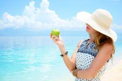 La giovane bella donna europea sta tenendo la mela verde in sua mano contro il mare tropicale molle calmo sotto il blu tenero Immagine Stock