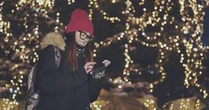 La giovane bella donna facendo uso della tenuta all'aperto nella notte della città, sorridente, fronte della mano dello Smart Pho stock footage