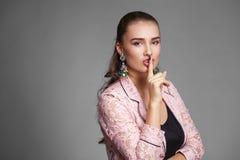 La giovane bella donna ha messo l'indice alle labbra come segno di sil Immagini Stock