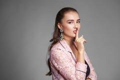 La giovane bella donna ha messo l'indice alle labbra come segno di sile Fotografia Stock