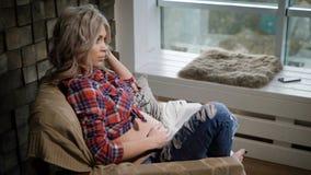 La giovane bella donna incinta in camicia e blue jeans di plaid si siede nel armchairm vicino alla finestra Lei che gioca i suoi  archivi video