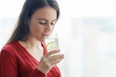 La giovane bella donna in maglione rosso con bicchiere d'acqua con calce, donna sta vicino alla finestra in grattacielo il giorno immagini stock
