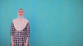 La giovane bella donna musulmana nella maschera medica, decolla la maschera sorridente ed esaminante la macchina fotografica video d archivio