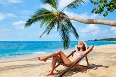 La giovane bella donna prende il sole e si rilassa sulla spiaggia tropicale fotografie stock libere da diritti