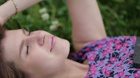La giovane bella donna raddrizza i suoi capelli che si trovano sull'erba Fine in su stock footage