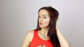 La giovane bella donna raddrizza i vestiti, guarda in specchio archivi video