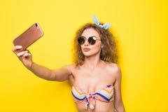 La giovane bella donna riccia con il sorriso felice in occhiali da sole prende Fotografia Stock Libera da Diritti