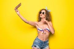 La giovane bella donna riccia con il sorriso felice in occhiali da sole prende il selfie sul telefono su fondo giallo Fotografie Stock Libere da Diritti