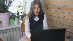 La giovane bella donna scrive sul computer portatile la risposta al suo cliente stock footage
