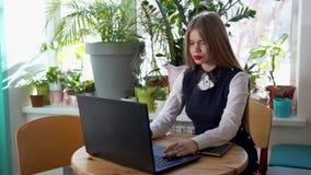 La giovane bella donna scrive sul computer portatile la risposta al suo cliente archivi video