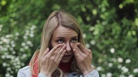 La giovane bella donna sfrega i suoi occhi che stanno contro lo sfondo degli alberi di fioritura Allergia, rinite, malattie dell' video d archivio