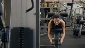 La giovane bella donna si esercita sui tendini del ginocchio nel club di forma fisica video d archivio