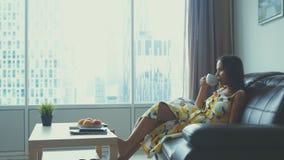 La giovane bella donna si rilassa sul sofà di cuoio a casa che guarda il tè di sorrisi e delle bevande di un film immagini stock libere da diritti