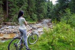 La giovane, bella donna si siede su una bicicletta, contro il contesto di un fiume della montagna immagine stock