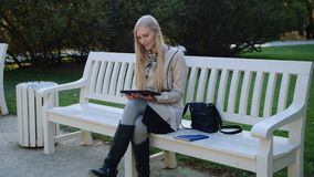 La giovane bella donna si siede sul banco in Autumn Park And Works On la compressa stock footage