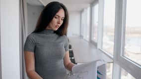 La giovane bella donna sta esaminando il progetto che sta nell'ufficio moderno video d archivio