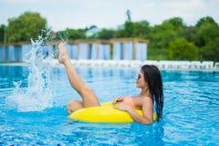 La giovane bella donna sta rilassandosi nella piscina con l'anello di gomma fotografia stock