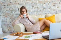 La giovane bella donna sta sedendosi su un sofà su un fondo bianco del muro di mattoni con una tazza di caffè Computer portatile, fotografia stock libera da diritti