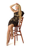 La giovane bella donna sta sedendosi sull'alta presidenza di legno. Immagini Stock