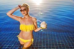 La giovane bella donna sta stando in bikini con la noce di cocco fresca Fotografia Stock