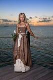 La giovane bella donna su una piattaforma di legno sopra il mare Fotografia Stock Libera da Diritti