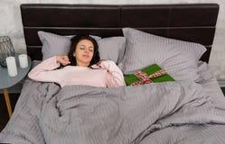La giovane bella donna sveglia ed allungando a letto e christma Fotografie Stock Libere da Diritti