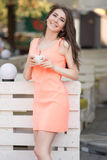 La giovane bella donna tiene la tazza di tè in caffè Immagini Stock