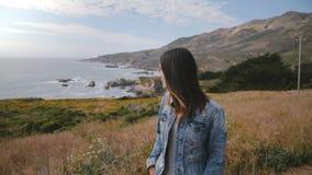 La giovane bella donna triste sembra depressa e giù la camminata sulla costa epica dell'oceano del Big Sur coperta di fiori giall video d archivio