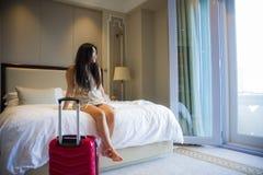 La giovane bella donna turistica coreana asiatica felice con la valigia di viaggio è arrivato appena sedendosi al letto dell'hote immagini stock