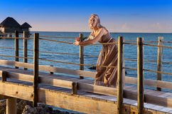 La giovane bella donna in un vestito lungo sulla strada di legno sopra il sea.portrait contro il mare tropicale Fotografie Stock