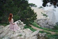 La giovane bella donna in un vestito rosa lungo si siede su una scogliera di un'alta montagna Fotografia Stock Libera da Diritti