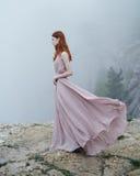 La giovane bella donna in un vestito rosa lungo sta stando su una scogliera di alta roccia nella nebbia Fotografia Stock