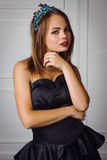 La giovane bella donna in vestito nero ed il diamante incoronano fotografia stock
