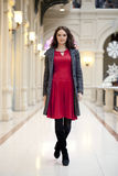 La giovane bella donna in vestito rosso cammina nel deposito Fotografia Stock Libera da Diritti