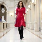 La giovane bella donna in vestito rosso cammina nel deposito Fotografie Stock Libere da Diritti
