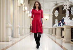 La giovane bella donna in vestito rosso cammina nel deposito Immagini Stock Libere da Diritti