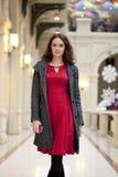 La giovane bella donna in vestito rosso cammina nel deposito Fotografie Stock