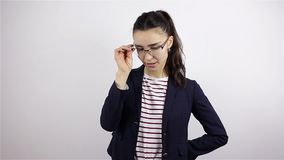 La giovane bella donna in vetri esamina la macchina fotografica e sbatte le palpebre archivi video