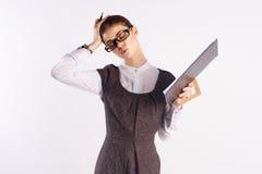 La giovane bella donna in vetri su antecedenti bianchi tiene una cartella con i documenti, l'insegnante, Immagini Stock