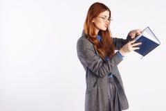 La giovane bella donna in vetri sugli antecedenti bianchi, insegnante, insegna a, Fotografia Stock